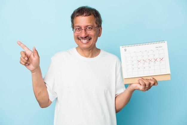 Senior indiase man met een kalender geïsoleerd op een blauwe achtergrond glimlachend en opzij wijzend, met iets op lege ruimte.