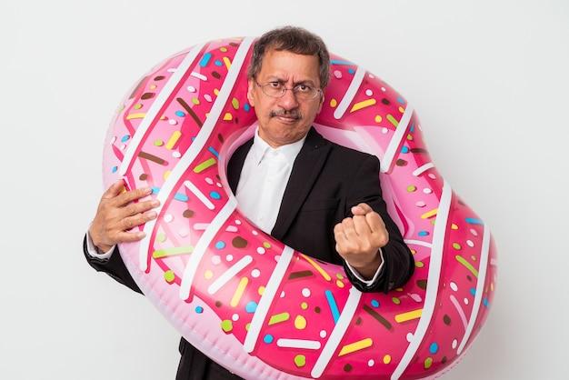 Senior indiase zakenman met opblaasbare donut geïsoleerd op een witte achtergrond met vuist naar camera, agressieve gezichtsuitdrukking.