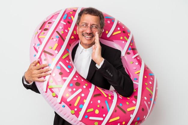 Senior indiase zakenman met opblaasbare donut geïsoleerd op een witte achtergrond zegt een geheim heet remnieuws en kijkt opzij