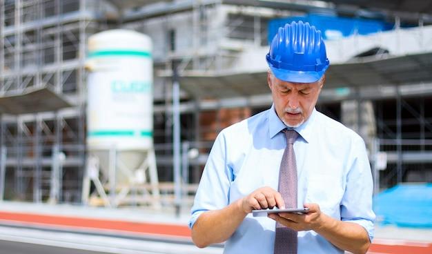 Senior ingenieur man in pak en helm werken op tablet pc