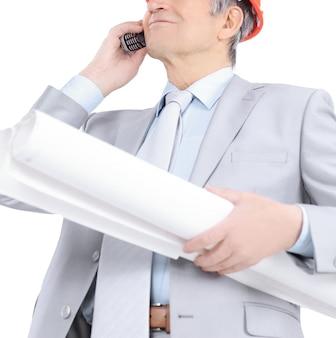 Senior ingenieur met blauwdrukken praten over de mobiele telefoon.