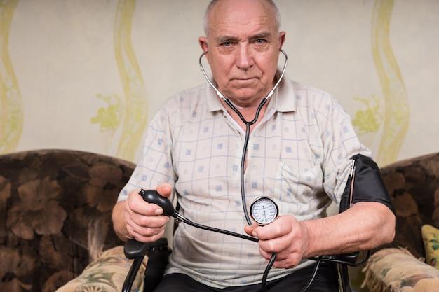 Senior kale man met speciale behoeften, zittend op zijn rolstoel en bloeddrukmeter en stethoscoopapparaat vasthoudend, recht in de camera kijkend.