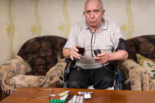 Senior kale man met speciale behoeften, zittend op zijn rolstoel in de woonkamer, kijkend naar de camera terwijl hij een gezond sapdrankje en bp-apparaat vasthoudt