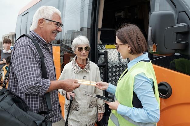 Senior kaukasisch koppel staat bij open busdeur en toont kaartjes aan bussupervisor met tablet