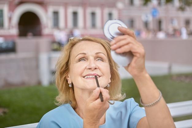 Senior kaukasische witte aantrekkelijke dame van ongeveer 60 jaar oud loopt in het centrum en maakt make-up met een zakspiegel.