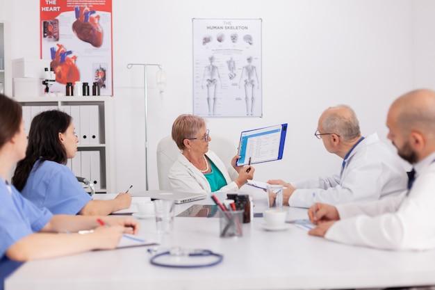 Senior kinderartsvrouw die ziektebehandeling bespreekt met klembord voor medische presentatie