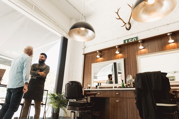 Senior klant en kapper bespreken over werk