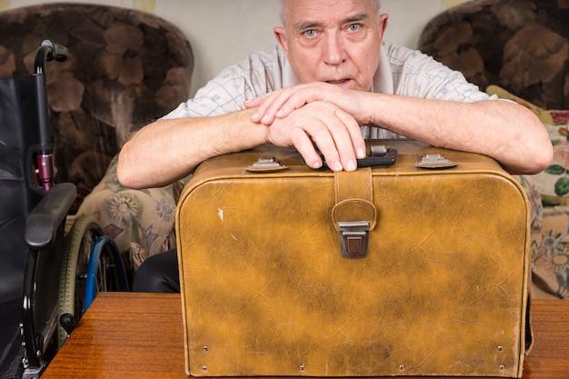 Senior kleermaker met speciale behoeften, leunend op zijn vintage naaimachinekoffer en kijkend naar de camera.