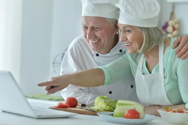 Senior koppel bij keuken koken met laptop