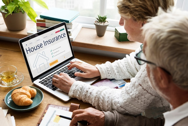 Senior koppel dat huisverzekering raadpleegt op de laptop