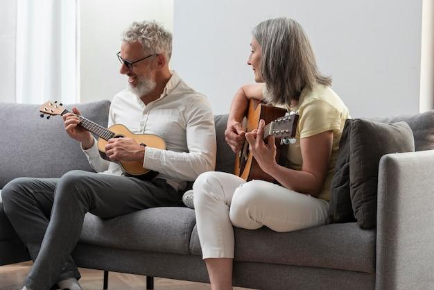 Senior koppel dat thuis gitaar- en ukelelelessen op laptop bestudeert