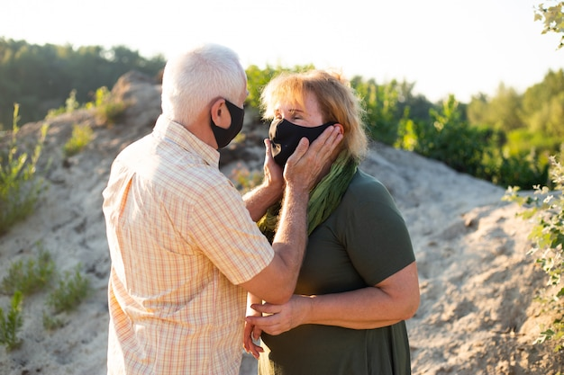 Senior koppel draagt medische maskers om te beschermen tegen coronavirus in zomerdag, coronavirus quarantaine