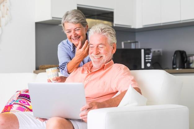 Senior koppel gaat samen op de bank zitten en gebruikt een laptop