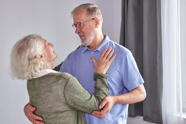 Senior koppel heeft plezier met dansen thuis, romantische volwassen grijsharige man en vrouw voelen zich energiek actief genieten van gezinsuitbreidingsweekend, samen vakantie doorbrengen