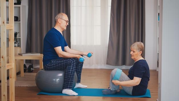 Senior koppel in woonkamer doet fysieke training op yogamat en stabiliteitsbal. oude persoon gezonde levensstijl oefening thuis, training en training, sportactiviteit thuis