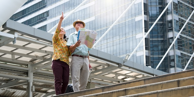 Senior koppel loopt, sleept hun bagage en houdt een kaart vast om door de straten te navigeren.