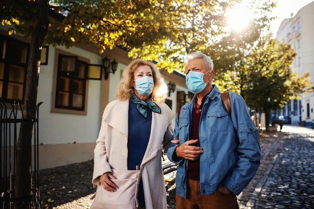 Senior koppel met beschermende maskers op samen wandelen in een oud deel van de stad.