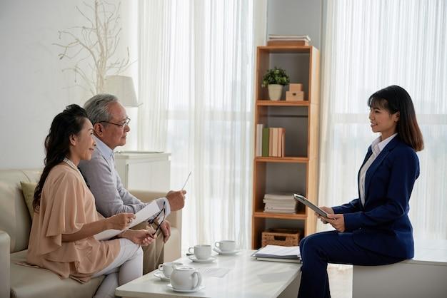 Senior koppel ontmoeting met vastgoedmanager die hen kan helpen om een huis te verkopen en een nieuwe te kopen