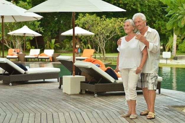 Senior koppel ontspannen in de buurt van zwembad in hotelresort
