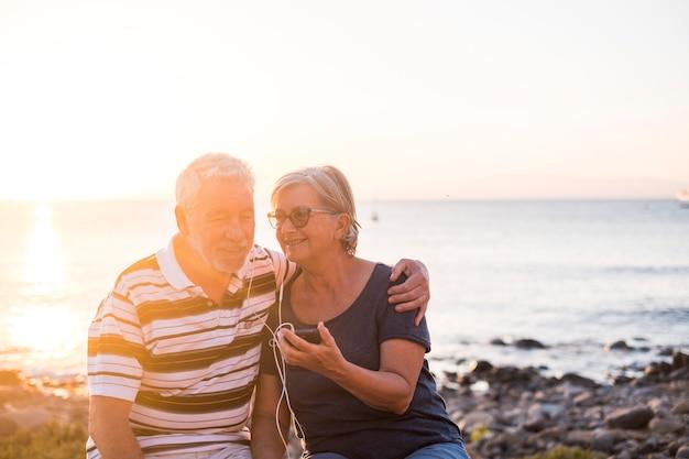 Senior koppel op het strand met zonsondergang - gepensioneerd echtpaar luistert samen met dezelfde koptelefoon naar muziek