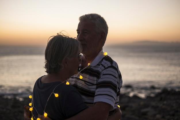 Senior koppel op het strand met zonsondergang - gepensioneerd echtpaar met licht eromheen - liefdes- en vredesmoment met zonsondergang