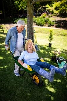 Senior koppel spelen met een kruiwagen