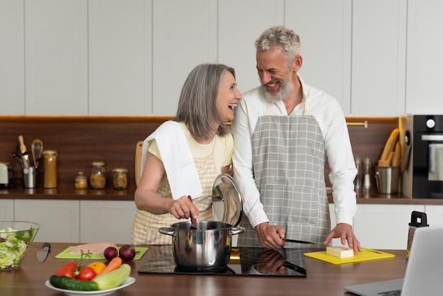 Senior koppel thuis in de keuken kooklessen nemen op laptop