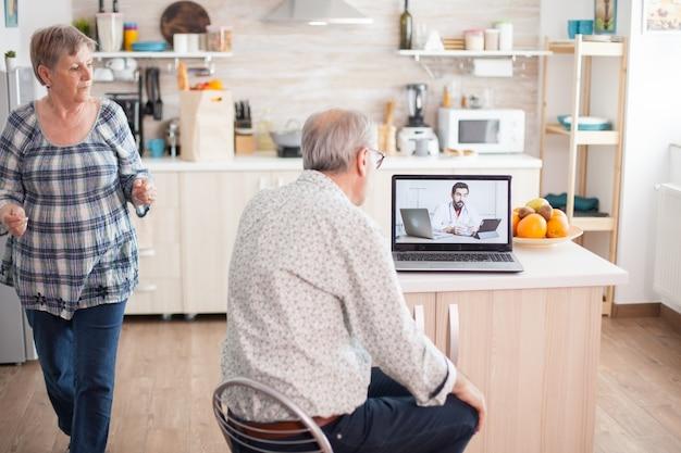 Senior koppel tijdens videoconferentie met arts die laptop in de keuken gebruikt om gezondheidsproblemen te bespreken. online gezondheidsconsultatie voor ouderen drugs ziekte advies over symptomen, arts tel