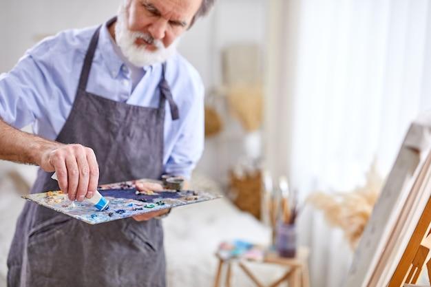 Senior kunstenaar perst verf uit een buis, focus op handen, in art studio