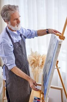 Senior kunstenaar schilderen op ezel, canvas, intelligente professionele schilder geniet van kunst