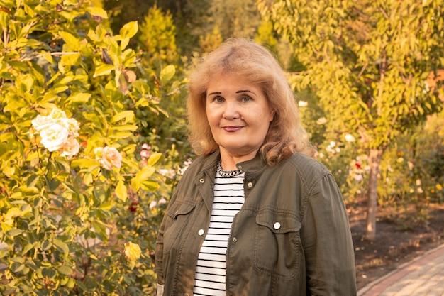 Senior lachende vrouw in park, gelukkig pensioen