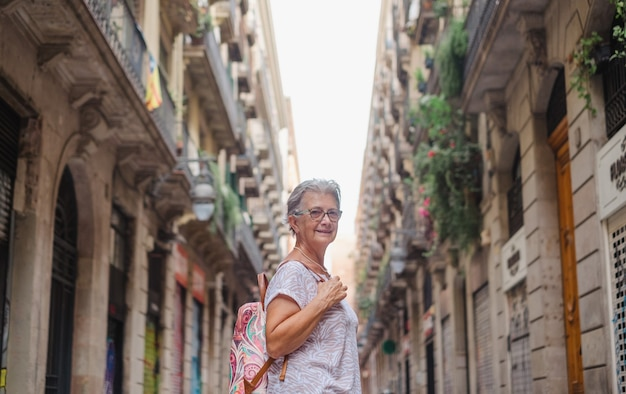 Senior lachende vrouw reist naar barcelona om het oude stadsdeel te bezoeken en te genieten van de vakantie