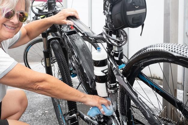 Senior lachende vrouw wast zijn fiets en zorgt voor de details. servicestation. hogedrukpomp