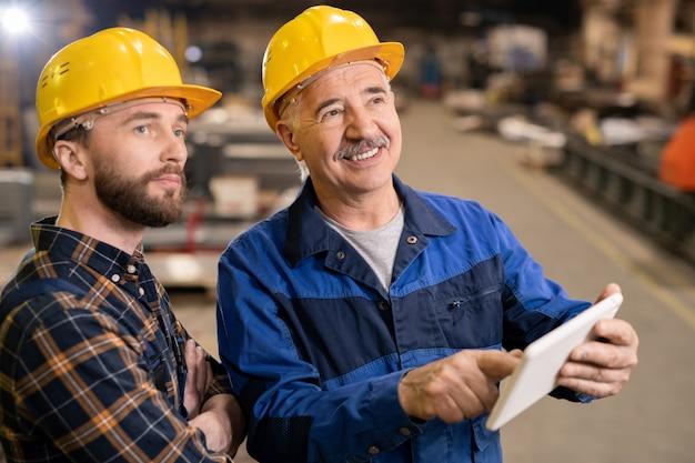 Senior lachende zakenman in veiligheidshelm en werkkleding wijzend op de weergave van touchpad terwijl hij en zijn stagiair industriële machine kijken