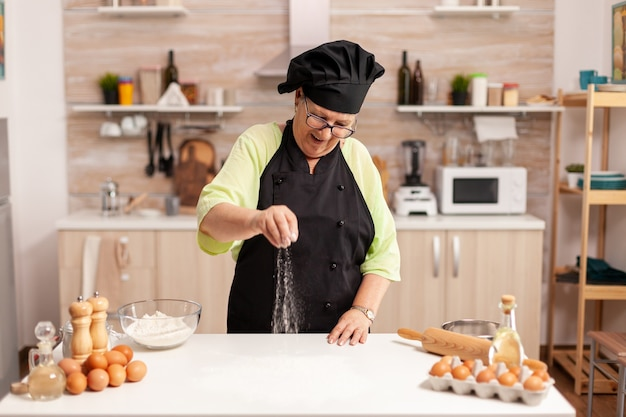 Senior lady chef glimlacht tijdens het bereiden van pizza bestrooiing meel op de keukentafel. gelukkige bejaarde chef-kok met uniform besprenkelen, zeven met de hand zeven van ruwe ingrediënten.