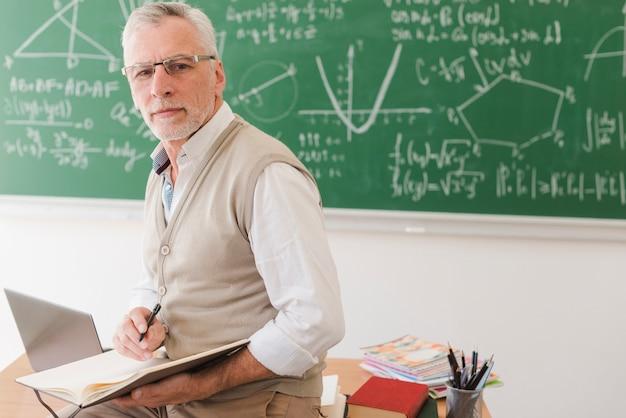 Senior leraar zittend op een bureau en schrijven in notitieblok