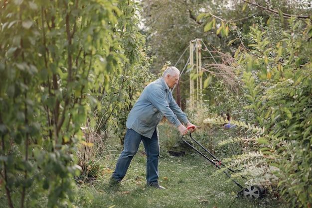 Senior maait het gras in de tuin met een grasmaaier