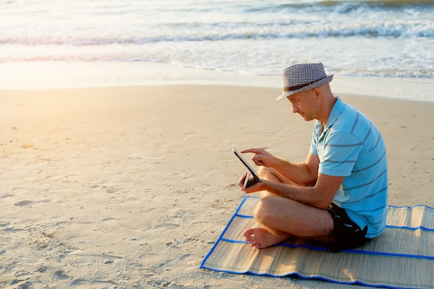 Senior man aan het werk op zijn laptop op het strand zee tijdens zonsondergang