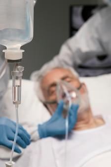 Senior man ademen met een speciale uitrusting in het ziekenhuis
