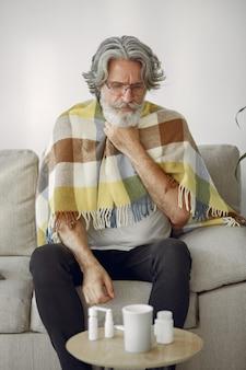 Senior man alleen zittend op de bank. zieke man bedekt met plaid. grangfather met kopje thee.