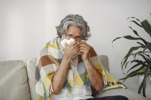 Senior man alleen zittend op de bank. zieke man bedekt met plaid.