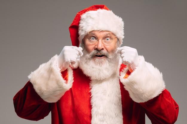 Senior man als de kerstman geïsoleerd op grijze studio achtergrond