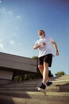 Senior man als hardloper met armband of fitnesstracker op straat in de stad. kaukasisch mannelijk model dat joggen en cardiotrainingen beoefent in de zomerochtend. gezonde levensstijl, sport, activiteitenconcept.