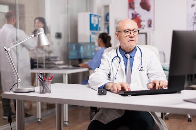 Senior man arts met grijs haar die op de computer werkt terwijl een jonge collega met een patiënt in de ziekenhuisgang is en een verpleegster die het analyserapport controleert.