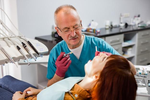 Senior man arts tandarts in zijn kliniek kijken naar de patiënt vrouw, tandarts is klaar om lokale anesthesie injectie te geven aan de vrouw