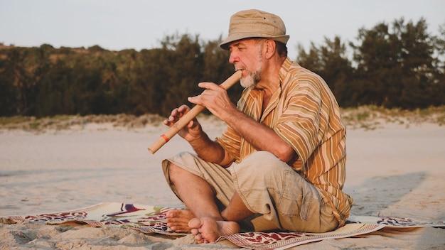 Senior man bamboe fluit spelen op het zandstrand bij zonsondergang licht