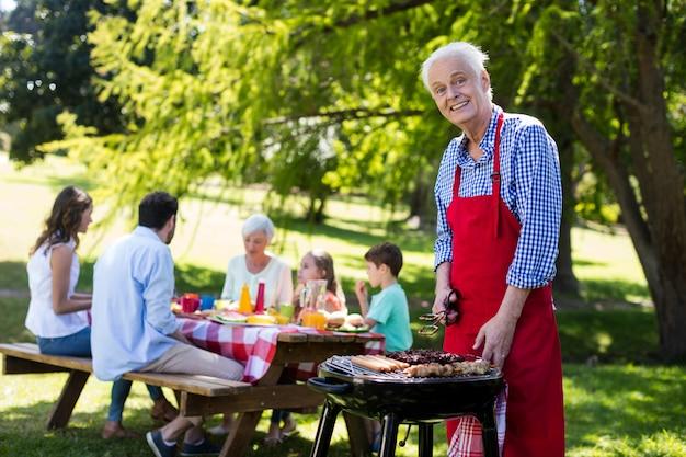 Senior man barbequen met familie op achtergrond