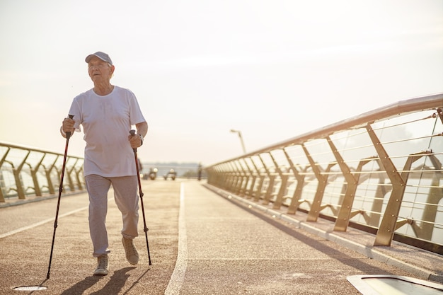 Senior man beoefent nordic walking met stokken op lege voetgangersbrug