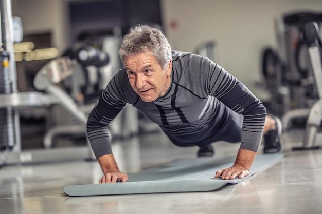 Senior man blijft fit door push-ups te doen op een mat in het fitnesscentrum.