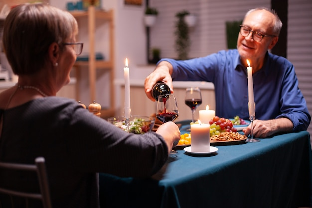 Senior man chatten met vrouw en rode wijn gieten. bejaard echtpaar zittend aan tafel in de keuken, pratend, genietend van de maaltijd, hun jubileum vierend in de eetkamer.